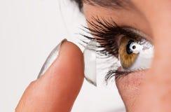 Junge Frau, die Kontaktlinse in ihr Auge einsetzt Lizenzfreies Stockfoto