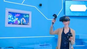 Junge Frau, die Kopfhörer der virtuellen Realität verwendet und mit speziellem Steuerknüppel zeichnet lizenzfreie stockbilder