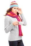 Junge Frau, die Kopfschmerzen hat und eine Tasse Tee anhält Lizenzfreie Stockfotografie