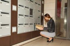 Junge Frau, die Korrespondenz vom Briefkasten nimmt stockbild