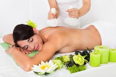 Junge Frau, die Kräuterball-Massage erhält Stockfotos
