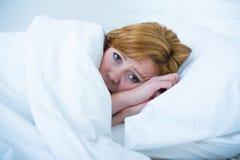 Junge Frau, die in krankem unfähigem des Betts, zu schlafen leidende Krise und schlafende Störung der Albtraumschlaflosigkeit lie stockbild