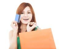 Junge Frau, die Kreditkarte mit Einkaufstasche anhält Stockfotos