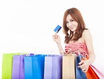 Junge Frau, die Kreditkarte mit Einkaufstaschen anhält Stockbilder