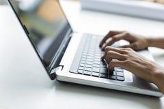 Junge Frau, die an Laptop arbeitet Stockfoto