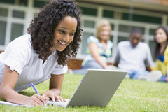 Junge Frau, die Laptop auf Campusrasen verwendet Lizenzfreie Stockbilder