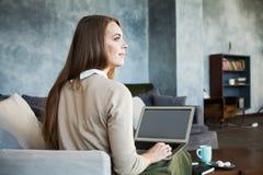 Junge Frau, die Laptop beim Sitzen auf bequemem Sofa verwendet Stockfotos