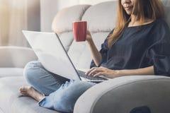 Junge Frau, die Laptop verwendet und Kaffee auf Sofa trinkt stockfoto