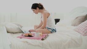 Junge Frau, die Laptop während des Frühstücks zu Hause sitzt auf weißem Bett verwendet Schreibenmitteilung des Brunettemädchens a Lizenzfreie Stockbilder