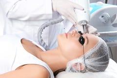 Junge Frau, die Laser-Abbau des dauerhaften Makes-up im Salon durchmacht Lizenzfreies Stockbild