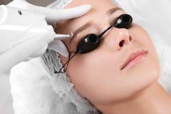 Junge Frau, die Laser-Abbau des dauerhaften Makes-up im Salon durchmacht Lizenzfreies Stockfoto