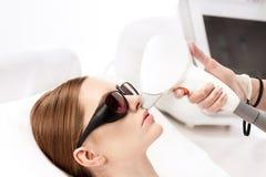 Junge Frau, die Laser-Haarabbau epilation auf dem Gesicht lokalisiert auf Weiß empfängt Lizenzfreie Stockfotos
