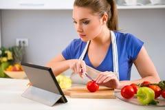 Junge Frau, die Lebensmittel zubereitet und Tablette betrachtet Stockfotos