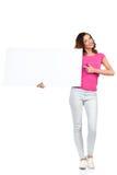 Junge Frau, die leeres Plakat und das Zeigen hält Lizenzfreie Stockfotos