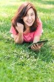 Junge Frau, die Legen der Tablette das im Freien auf das Gras, lächelnd verwendet lizenzfreies stockbild