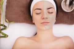 Junge Frau, die Lehmhaut-Maskenbehandlung auf ihrem Gesicht hat Stockfotografie