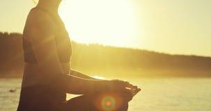 Junge Frau, die in Lotus-Haltung auf Flusspier bei gelbem Sonnenuntergang, Seitenansicht meditiert stock footage