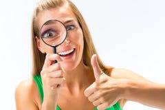 Junge Frau, die Lupe über den Augen sich zeigen Daumen hält lizenzfreie stockfotos