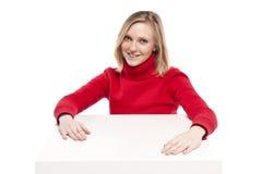 Junge Frau, die am lustigen kleinen Schreibtisch sitzt Stockfotografie