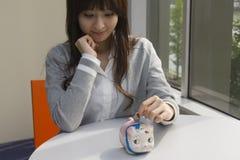 Junge Frau, die Münze in piggy Querneigung einsetzt lizenzfreies stockfoto