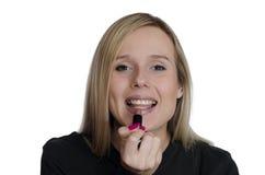 Junge Frau, die Make-up auf weißem Hintergrund verwendet Stockfotografie