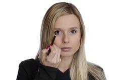 Junge Frau, die Make-up auf weißem Hintergrund verwendet Stockbild