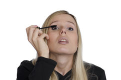Junge Frau, die Make-up auf weißem Hintergrund verwendet Lizenzfreies Stockfoto