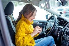 Junge Frau, die Make-up in einem Auto anwendet lizenzfreie stockfotografie