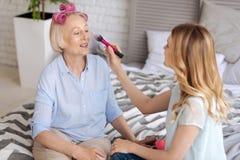 Junge Frau, die Make-up an ihrer Mutter anwendet Stockbilder