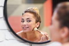 Junge Frau, die Make-up mit Bürste im Badezimmer anwendet stockbild