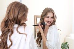 Junge Frau, die Make-up nahe Spiegel anwendet Lizenzfreie Stockfotos