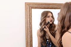 Junge Frau, die Make-up nahe Spiegel anwendet Stockbild