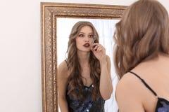 Junge Frau, die Make-up nahe Spiegel anwendet Stockfotografie