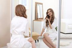 Junge Frau, die Make-up nahe Spiegel im Raum anwendet Lizenzfreie Stockbilder