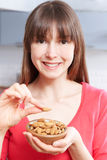 Junge Frau, die Mandeln von der Schüssel isst Lizenzfreie Stockbilder