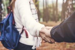 Junge Frau, die Mann ` s Hand hält und ihn auf Natur führt stockfoto