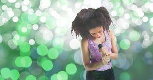 Junge Frau, die in Mikrofon gegen bokeh Hintergrund singt Stockfotografie
