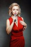 Junge Frau, die in Mikrofon singt Stockfotografie