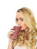 Junge Frau, die Misch-Berry Fruit Smoothie trinkt Stockfotografie