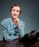 Junge Frau, die mit alter Schreibmaschine im Retrostil schreibt lizenzfreie stockfotos