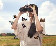 Junge Frau, die mit binokularem aufpasst Stockfotos