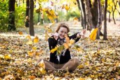 Junge Frau, die mit Blättern im Herbstpark spielt Stockfoto