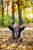 Junge Frau, die mit Blättern im Herbstpark spielt Lizenzfreies Stockfoto