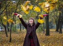 Junge Frau, die mit Blättern im Herbstpark spielt Stockfotos