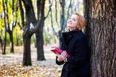 Junge Frau, die mit Buch im Herbstpark steht Lizenzfreie Stockbilder