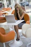 Junge Frau, die mit Computer in einem Kaffee arbeitet Lizenzfreies Stockfoto