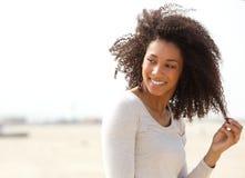 Junge Frau, die mit dem gelockten Haar lächelt stockbild