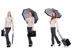 Junge Frau, die mit dem Koffer und Regenschirm lokalisiert auf wh reist Lizenzfreie Stockfotos