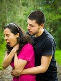 Junge Frau, die mit dem Mann steht hinter der Ausführung von heimlich Manöver, von Parkumwelt und von zufälliger Kleidung erdross lizenzfreie stockfotos