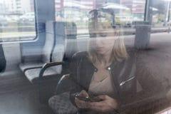 Junge Frau, die mit dem Zug, unter Verwendung des intelligenten Telefons reist Stockfoto